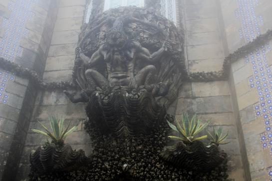 A triton emerges from a clamshell above a gate in the Pena National Palace in Sintra, Portugal.