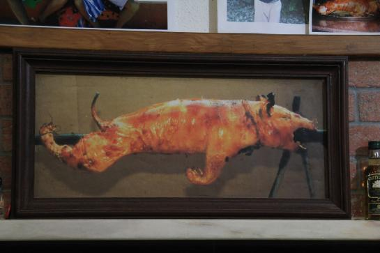 A photograph of a roasting pig sits above customers at the Porta Larga restaurant in Coimbra, Portugal.