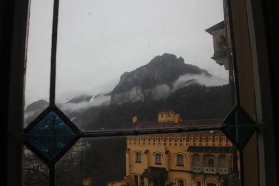 Neuschwanstein Castle can be seen through a window in Hohenschwangau Castle.