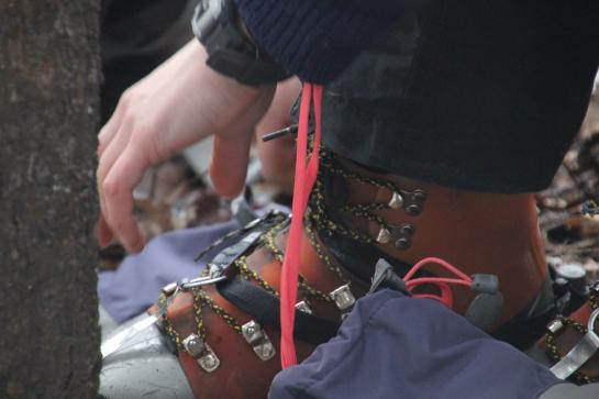 A hiker affixes crampons to a double-plastic mountaineering boot.