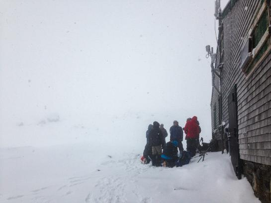 Hikers huddle next to the Lake of the Clouds Hut below Mount Washington's summit cone.