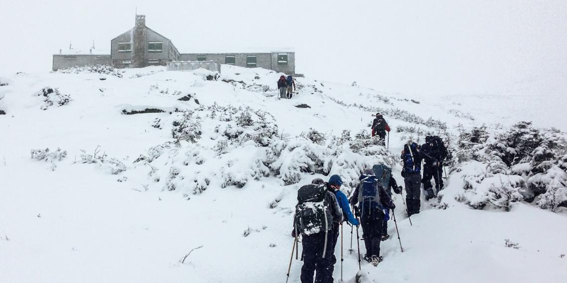 Hikers catch a glimpse of the Lake of the Clouds Hut below Mount Washington's summit.