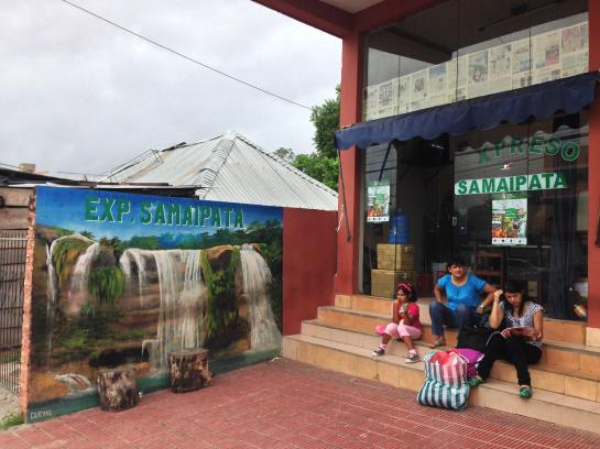 A Bolivian family sits outside an office that organizes carpools to El Fuerte de Samaipata in Santa Cruz, Bolivia.