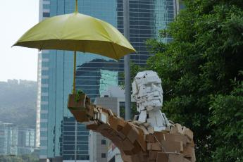 A sculptured man with an umbrella stands at Occupy Central in Hong Kong.