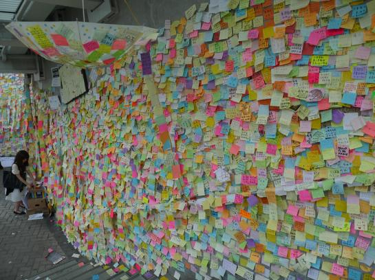 A woman adds a supportive message to the Lennon Wall Hong Kong.