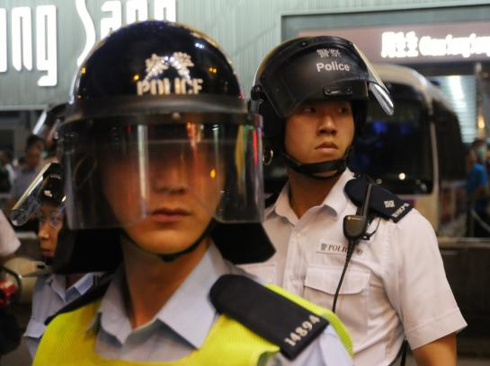 Hong Kong police don helmets and get ready to charge protesters in an attempt to clear the streets.