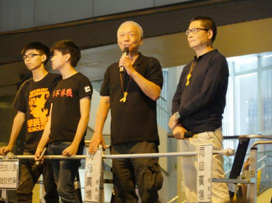 Occupy Hong Kong organizers Joshua Wong, Lester Shum, Chu Yiu-Ming, and Chan Kin-Man speak in front of a crowd.