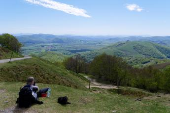 A pilgrim stops to rest and admire the view in the Spanish Pyrenees on the Camino de Santiago.