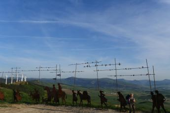 An art installation depicting pilgrims walking the Camino de Santiago sits on a ridge above Zariquiegui, Spain.