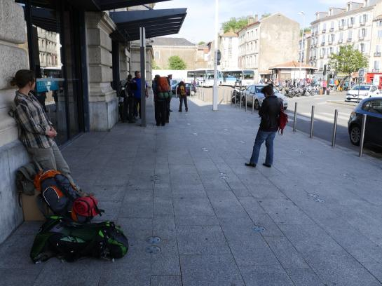 A young woman at the train station in Bayonne, France prepares to hike the Camino de Santiago while waiting for a bus to Saint-Jean-Pied-de-Port.