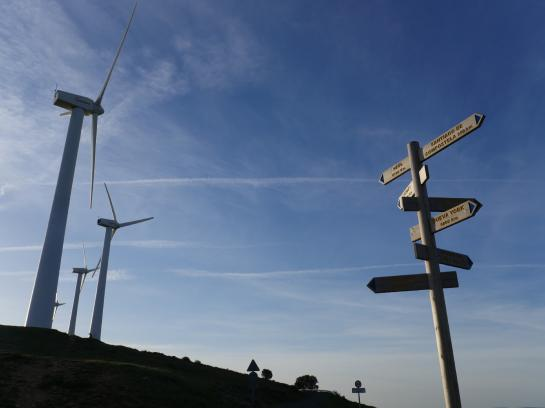 Signs point to the way to Santiago and other cities near windmills above Zariquiegui, Spain.
