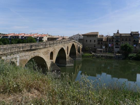 A famous, six-arched bridge allows hikers to cross the river in Puente La Reina, Spain.