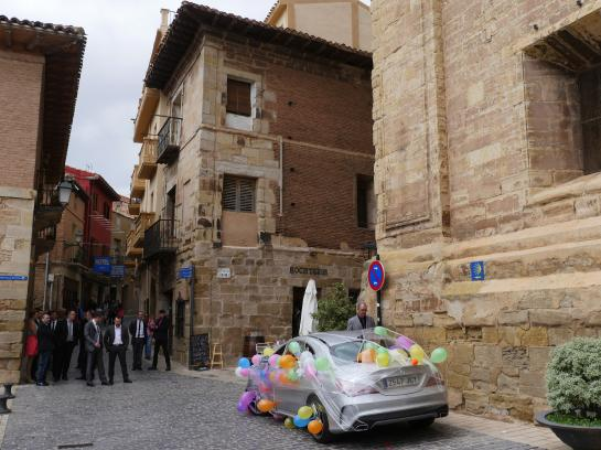 Groomsman and a decorated car sit outside the Iglesia de La Asunción in Navarrete, Spain in preparation for a wedding.