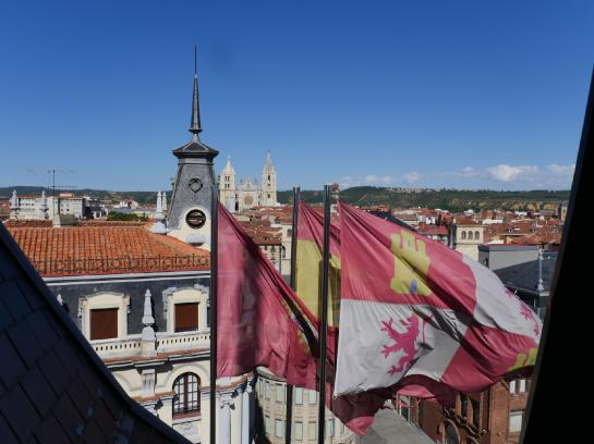 Flags wave in the wind outside a hotel room in León, Spain.