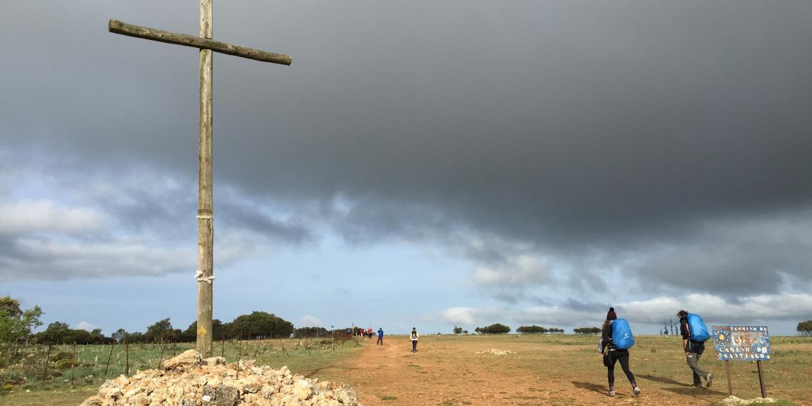 Hikers walk past a wooden cross above Atapuerca, Spain.