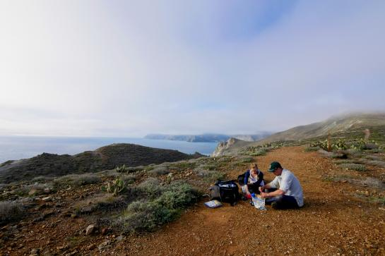 Hikers stop to eat lunch at a viewpoint above Little Harbor on the Trans-Catalina Trail.