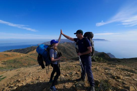 Hikers high-five at the Trans-Catalina Trail's high point at 1,800 feet.