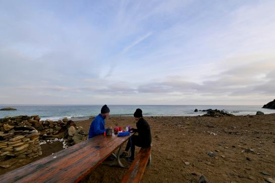 Hikers make coffee in the morning at a picnic table at Parsons Landing on Catalina Island, California.