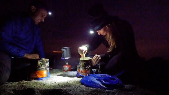 Hikers cook dinner at dusk above Starlight Beach at the end of the Trans-Catalina Trail on Catalina Island, California.