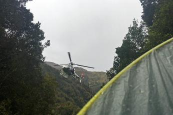 A rescue helicopter hovers above a ravine on the Toaroha Track on New Zealand's South Island.