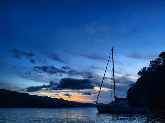 The sun sets over Kumutoto Bay in Queen Charlotte Sound, New Zealand.