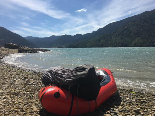 A packraft sits on a shoreline in Mahau Sound, New Zealand.