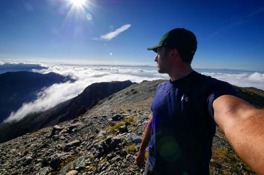Hank admires the view above the clouds from the top of Mount Rintoul in New Zealand's Richmond Range.