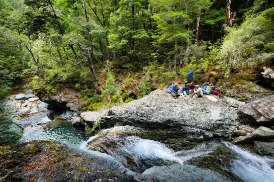 Te Araroa hikers eat lunch amongst waterfalls on the Pelorus River in New Zealand's Richmond Range.
