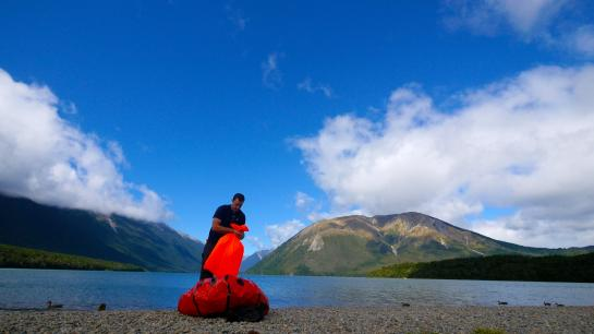 A rafter at Lake Rotoiti in St. Arnaud inflates a packraft by trapping air in a fabric bag and then squeezing the air into the raft.