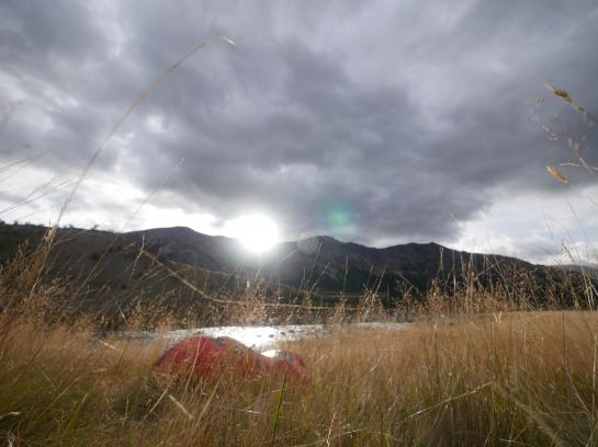 A packraft sits next to the Waiau River.