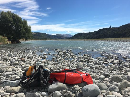 My packraft sits on the shore below the SH73 highway as I search for an access road to escape.