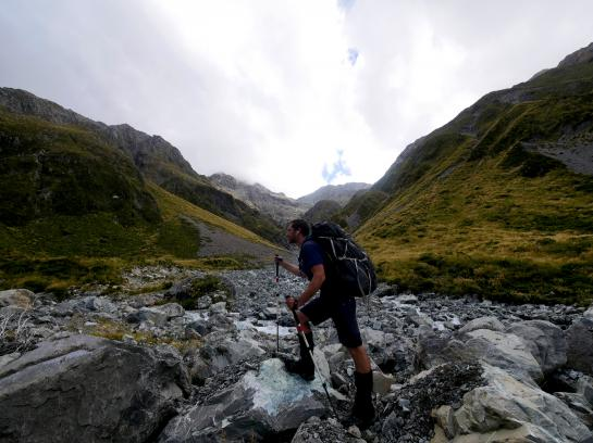 A hiker hikes up Harman Pass toward Whitehorn Pass in Arthur's Pass National Park, New Zealand.