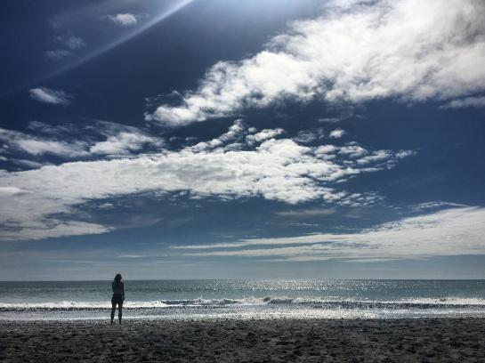 Charlotte stands on the beach in Hokitika.