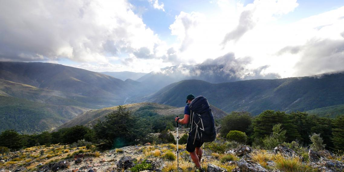 A hiker looks out from a ridge above Slaty Hut in New Zealand's Richmond Range.