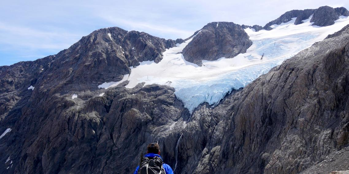 A hiker looks at Cronin Glacier above Whitehorn Pass in Arthur's Pass National Park, New Zealand.