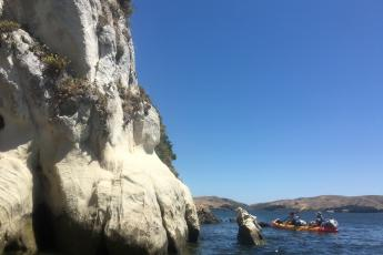 Kayakers paddle near White Gulch Beach in Tomales Bay, California.