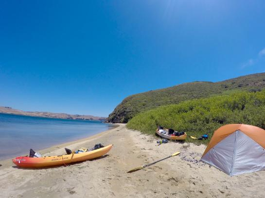 Kayaks and a tent sits sits on a beach in Tomales Bay, California.